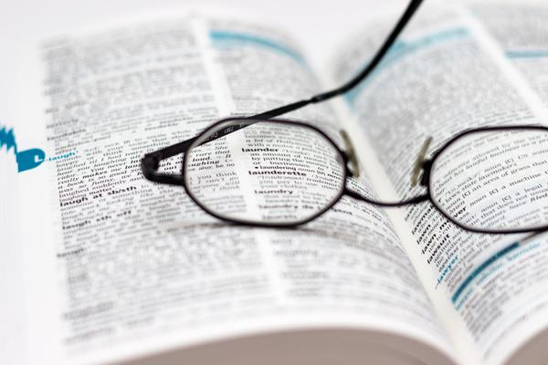 zeigt eine Brille auf einem Buch